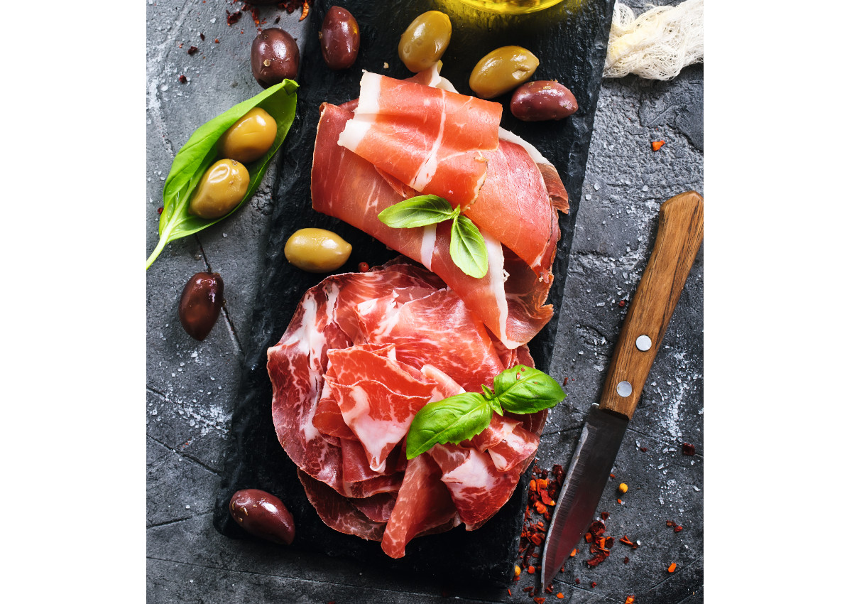 deli meats-prosciutto with olives and spice on a table